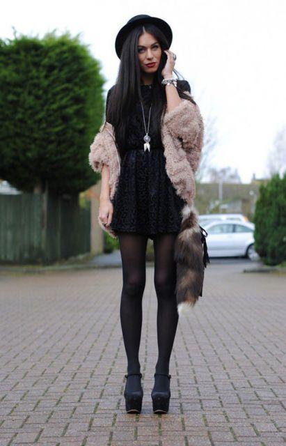 Modelo usa vestido preto, meia calça transparente preta, casaco de pelo nude, sapato de salto preto e chapéu feminino.