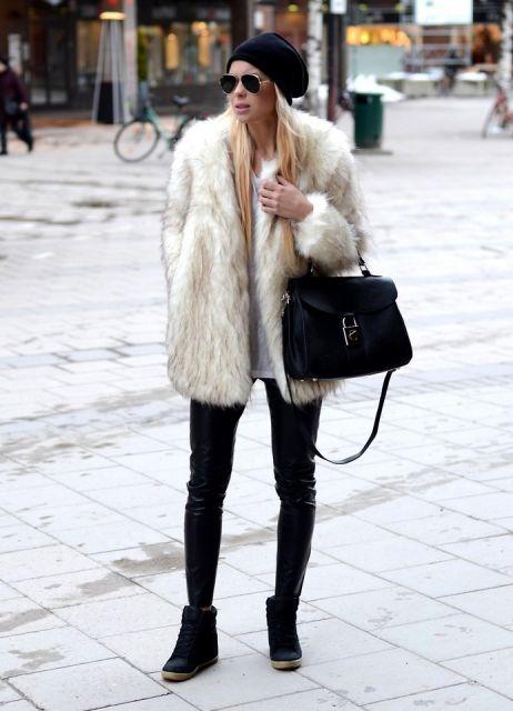 Look com modelo de calça preta, tenis preto, casaco de pele branco e bolsa preta de mão.
