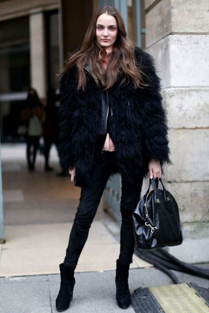 Modelo veste calça preta, casaco preto de pelos, tenis e bolsa na mesma cor.