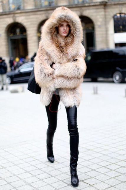 Modelo usa calça preta de couro,casaco de pelinhos bege e bolsa preta.