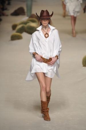 Modelo veste vestido branco estilo camisa, cinto marrom, colar botas e chapéu country na mesma.