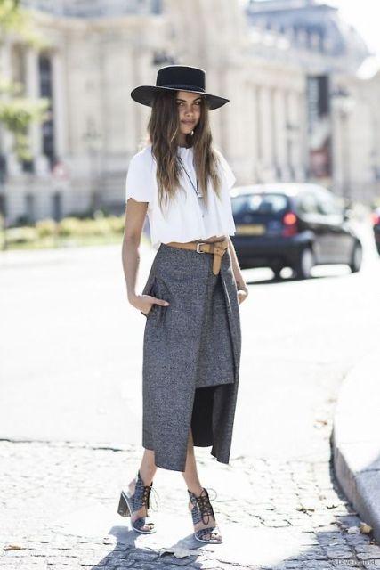 Modelo usa saia midi cinza, cropped branco, chapeu pralana preto e botinha preta.