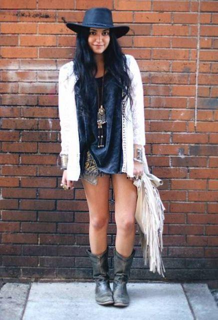 Modelo usa botas pretas, chapéu preto country, saia, camiseta e jaqueta branca.