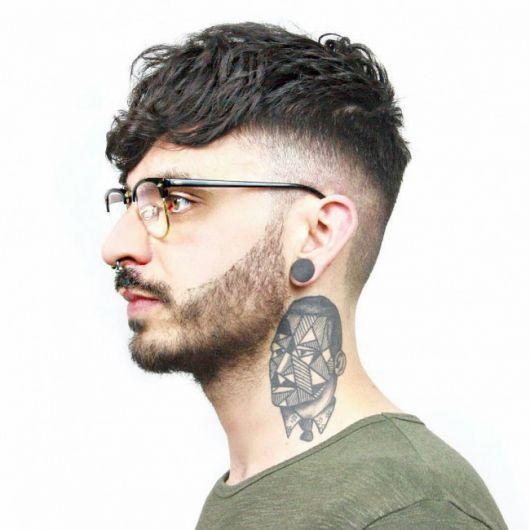 Homem de perfil com óculos, barba pequena, piercing no septo, alargador, tatuagem no pescoço e cabelo undercut bem raspado na lateral.
