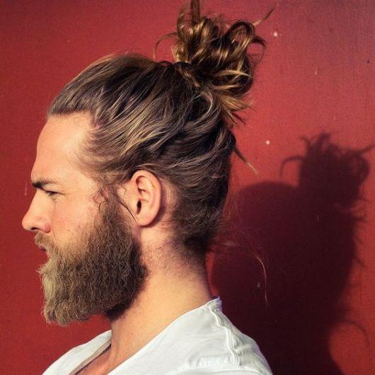 Homem de perfil com barba grande e coque no topo da cabeça feito com muito cabelo.