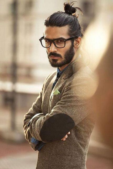 Homem de óculos e roupa social com barba bem feita e coque de cabelo longo.