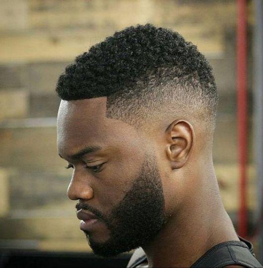 Homem de perfil com corte militar afro de barba bem feita que faz um degradê com a lateral do cabelo.