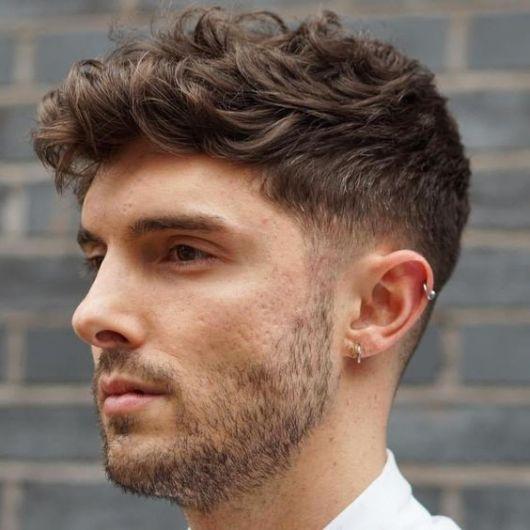 Homem com undercut em cabelo ondulado, que faz um topete discreto jogado para o lado.