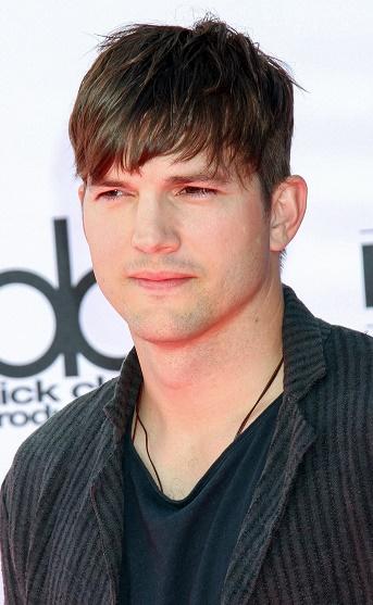 O ator Ashton Kutcher com franja repicada e laterais raspadas.
