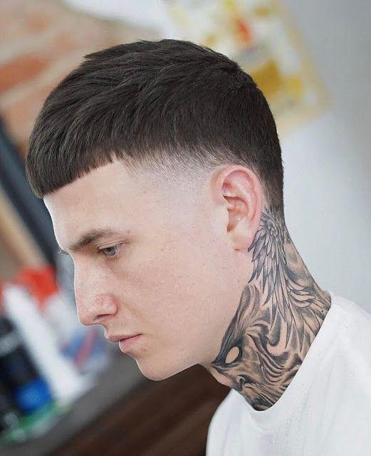 Homem de perfil com tatuagem no pescoço e corte caesar, com a franja bem pequena e um pequeno degradê na lateral.