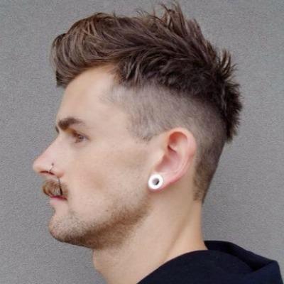Homem de perfil com alrgador e piercing no nariz. Seu cabelo é arrepiado no topo e raspado na lateral, com uma marca bem definida entre a parte mais curta e a mais longa.