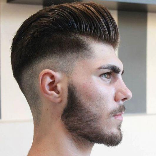 Homem de perfil com corte pompadour bem alto.