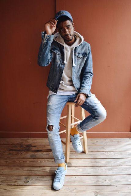 Homem sentando em um banco de madeira. Ele veste uma calça com jeans desgastado, moletom fechado com gorro e uma jaqueta jeans aberta por cima.