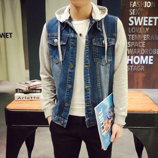 Foto do tronco de um homem segurando uma revista. Ele veste uma jaqueta jeans com gorro e mangas feitas de moletom.