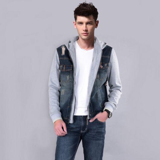 Homem vestindo uma calça jeans e uma camiseta branca sem estampa com uma jaqueta jeans com as mangas e sua parte interna feitas de moletom.