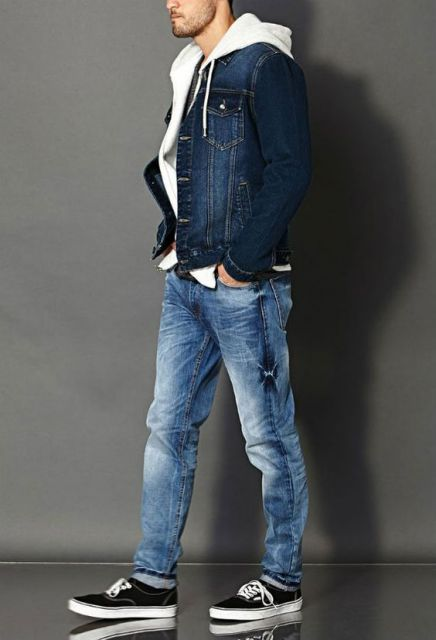 Homem de perfil vestindo uma calça jeans, blusa de moletom aberta com gorro e uma jaqueta de jeans escura por cima.