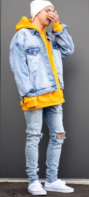 Homem com mão em frente ao rosto de lado para a câmera. Ele veste um gorro, um moletom grande e largo de cores muito vivas e uma jaqueta jeans com uma calça jeans, ambas do mesmo tom de cor.