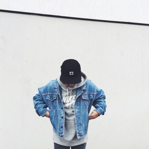 Homem olhando para baixo. Ele usa um boné, moletom fechado da Nike e uma jaqueta jeans aberta.