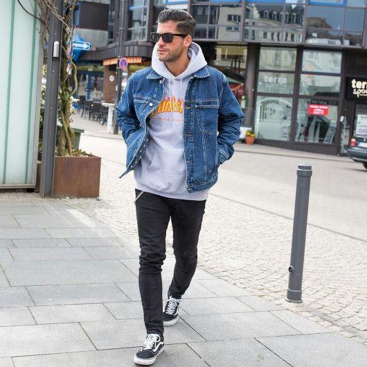 Homem caminhando na rua. Ele usa óculos escuros, cabelo penteado com gel, calça skinny, tênis clássico da van e um moletom da thrasher com uma jaqueta jeans por cima.