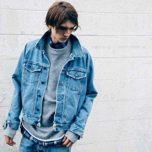 Homem com cabelo longo olhando para baixo. Ele veste uma camiseta xadrez de flanela com um moletom largo por cima e uma jaqueta jeans clara sobreposta a ele.