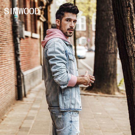 Homem olhando para trás enquanto caminha na rua. Ele veste um moletom com gorro e uma jaqueta jeans por cima, ambos com as mangas arregaçadas.