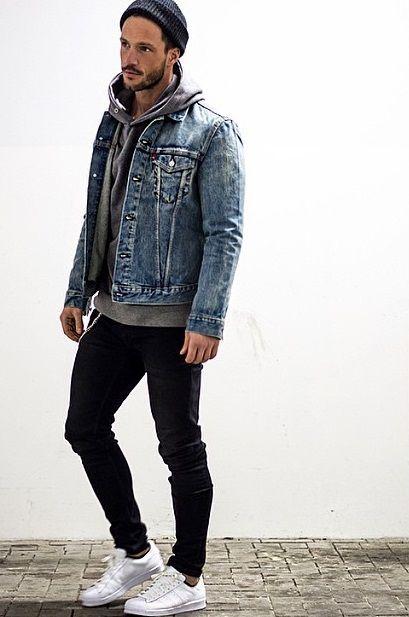 Homem vestindo um gorro, calça skinny escura e um moletom com gorro com jaqueta jeans por cima.