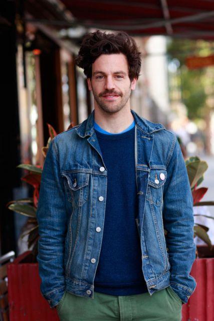 Homem vestindo um moletom sem estampa com uma jaqueta jeans por cima.