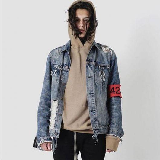 Homem vestindo um moletom com o gorro colocado em sua cabeça. Acima do moletom está sobreposta uma jaqueta com jeans desgastado e uma braçadeira com o número 42.