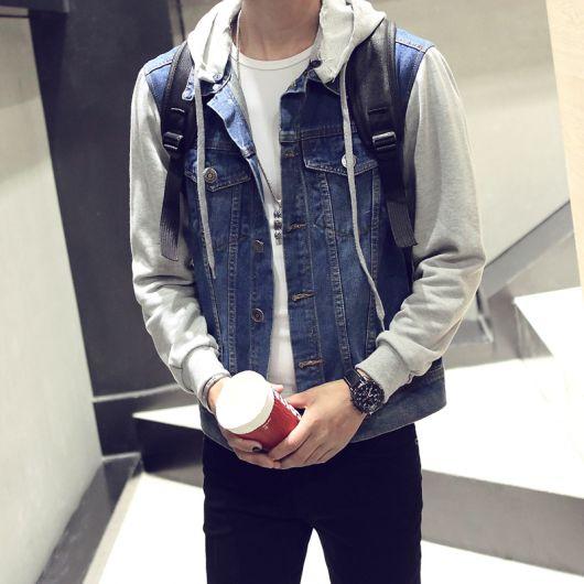 Foto do tronco de um homem segurando um copo com as duas mãos. Ele está vestindo uma jaqueta jeans com as mangas feitas de moletom.