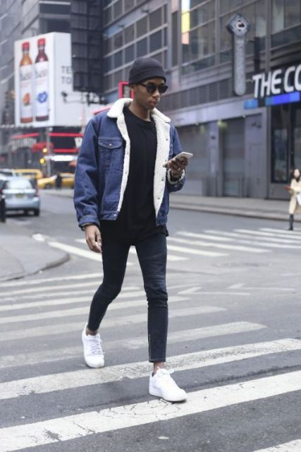 Homem de celular e gorro andando na rua enquanto olha seu celular. Ele veste uma calça skinny e moletom preto com uma jaqueta jeans escura por cima