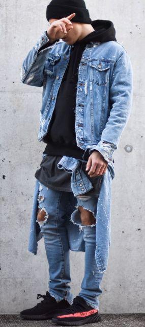 Homem de pé tampando o rosto. Ele veste um moletom fechado, calça jeans rasgada nos joelhos, jaqueta com jeans desgastado e uma outra jaqueta amarrada na cintura.