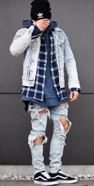 Homem de pé tampando o rosto. Ele está vestindo uma calça jeans rasgada e na parte superior um moletom fechado, uma blusa de flanela aberta e por cima das duas uma jaqueta jeans clara.