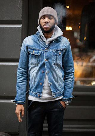 Homem de gorro vestindo um moletom fechado com uma jaqueta jeans por cima e os dois botões superiores dela fechados.