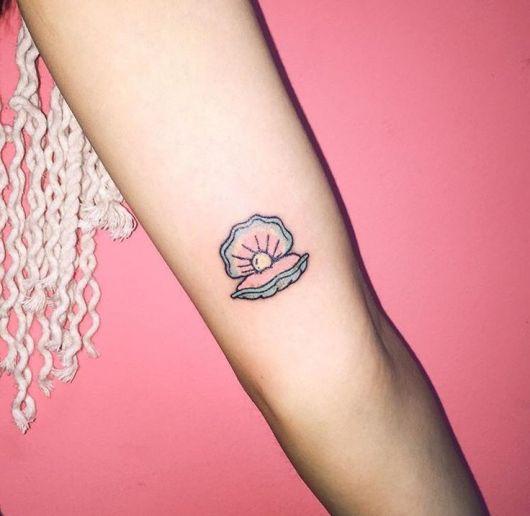 tatuagem de concha delicada no braço