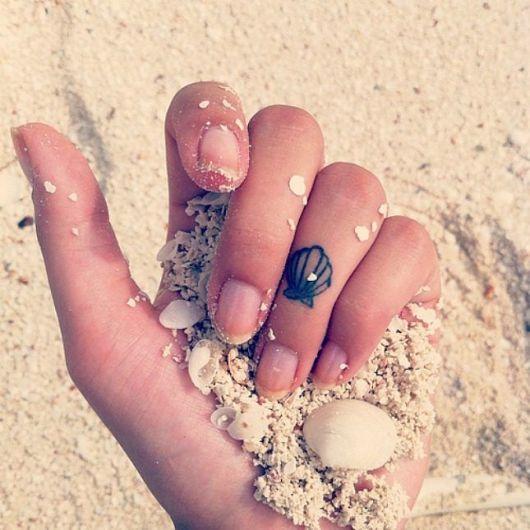 tatuagem de concha pequena no dedo