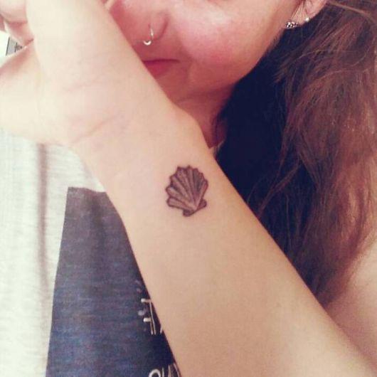 tatuagem de concha bem pequena no braço