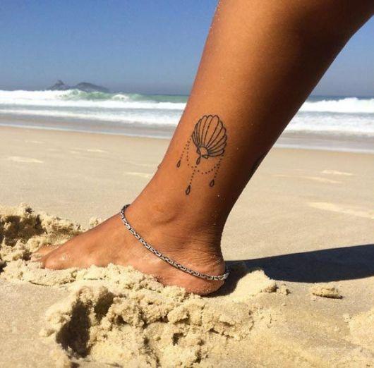tatuagem de concha quase no pé