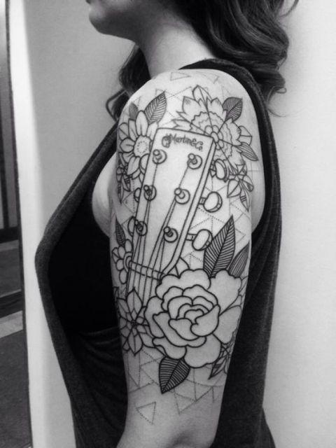 Tatuagem na parte superior do braço de uma mulher com a 'mão' de una guitarra e diversas flores ao seu redor.