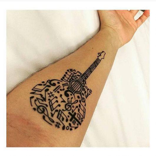 Tatuagem de um violão feita de forma abstrata. Não há contorno e seu interior é preenchido por notas musicais.