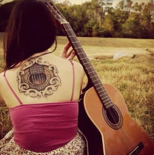 Tatuagem redonda no centro das costas de uma mulher acompanhada de seu violão. A tatuagem apenas revela a boca e parte das cordas do violão.