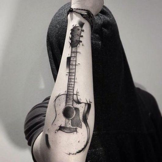 Homem com o rosto coberto e o braço levantado, onde há uma tatuagem de violão feita como se fosse um esboço na parte externa do antebraço.