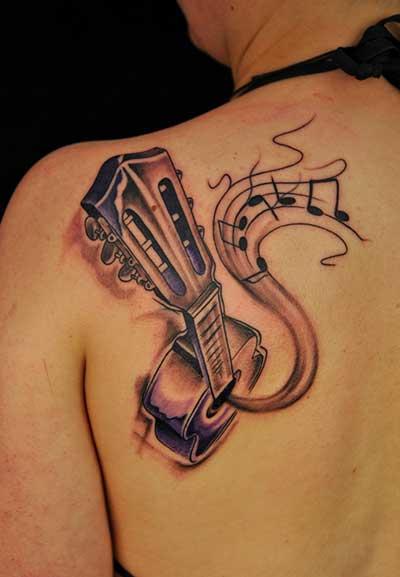 Tatuagem de um violão visto de cima com notas musicais saindo de sua boca feita na lateral das costas.