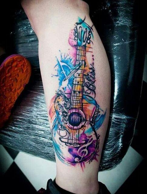 Tatuagem de uma guitarra na perna com muitas cores de aquarela e detalhes abstratos ao seu redor.