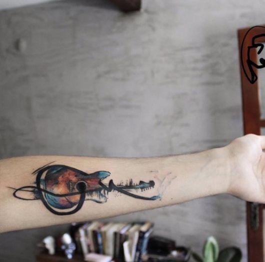 Tatuagem colorida no antebraço de um violão com uma linha sinuosa saindo de seu interior e rodeando-o por toda sua extensão.