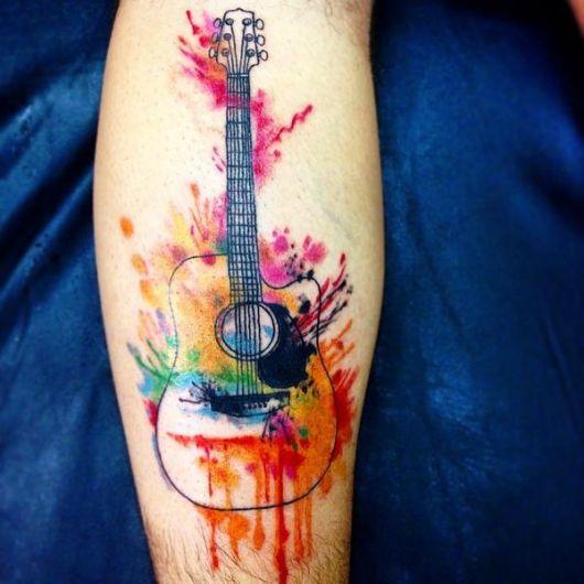 Tatuagem simples de um violão colorido com aquarela que simula uma pintura devido às cores jogadas randomicamente.