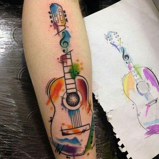 Tatuagem de um violão tradicional pintado com aquarela e uma nota musical que divide seu braço em dois.