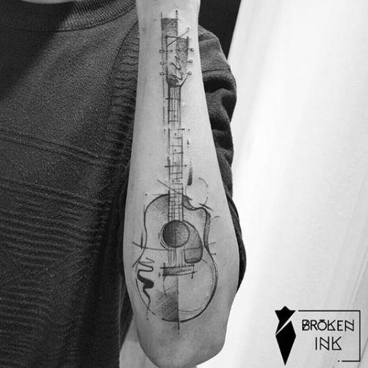 Tatuagem de violão na parte externa do antebraço. A forma como ele é desenhado lembra um esboço. Há diversas linhas e formas ao redor do violão.