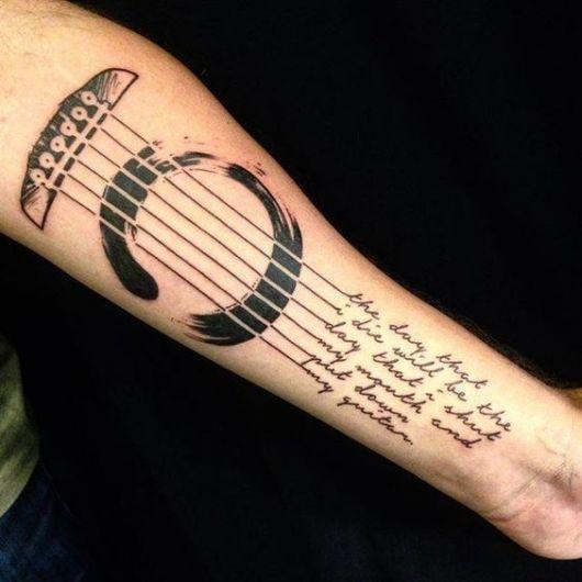 Boca de um violão, rastilho e cordas que se transformam em letras no final de sua extensão. Tatuagem feita no antebraço.
