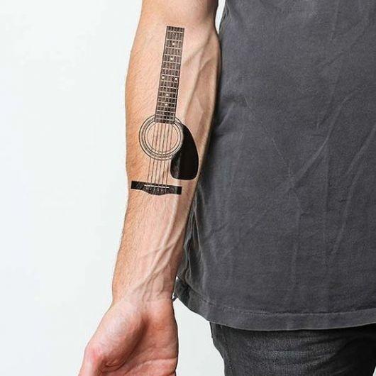 Tatuagem no antebraço de um homem com o desenho de um rastilho, boca, cordas e braço de um violão. Tudo sem contorno.