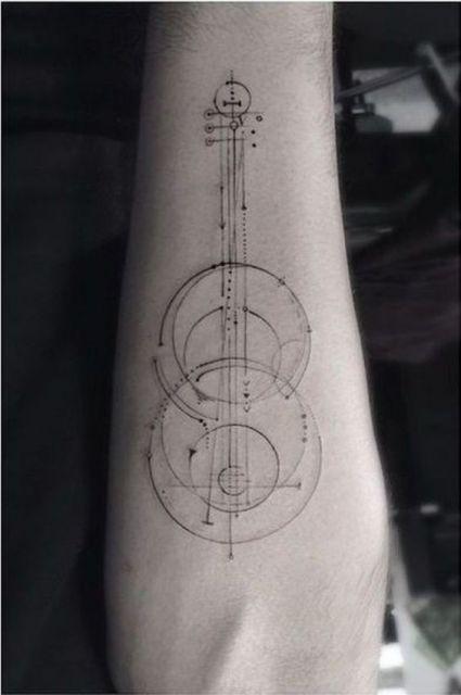 Tatuagem minimalista de um violão formado a partir de formas geométricas como linhas e círculos.